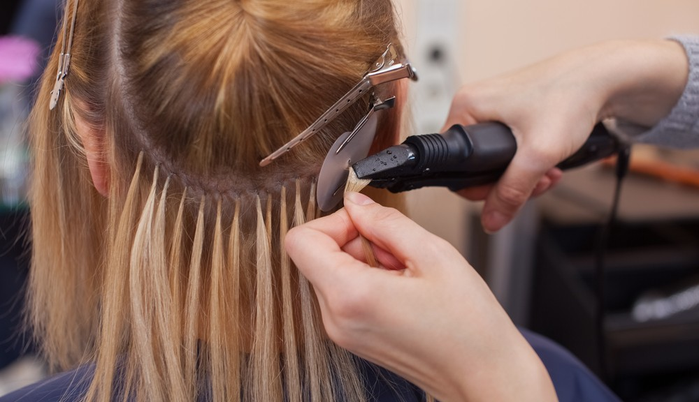 woman getting hair extensions put in
